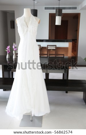 Beautiful white lace and silk wedding dress on a mannequin.