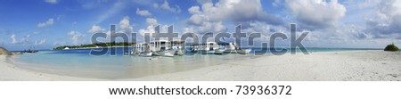 Beautiful white Maldivian beach and five dhoni ships docked nearby - stock photo