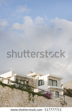 Beautiful white mansion behind a stone fence and a blue sky with clouds