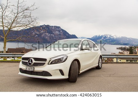 Beautiful white Mercedes parked by the side of the lake in Swiss Alps. Zurich, Switzerland. March 10, 2016