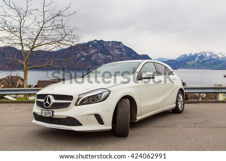 Beautiful white Mercedes parked by the side of the street near lake and mountains. - stock photo