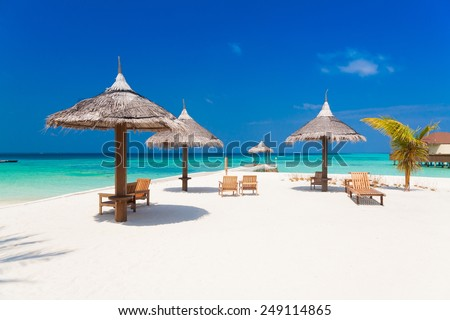 beautiful white parasol and sunbed in sea tropical  Maldives  romantic  atoll island paradise luxury  resort about coral reef - stock photo