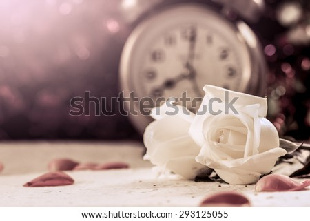 beautiful white rose on mulberry paper on alarm clock background in vintage color tone - stock photo