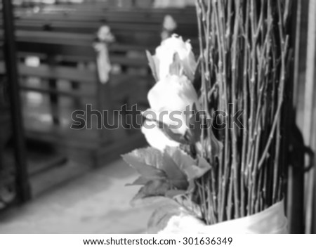Beautiful white roses  wedding decoration in the church. Retro aged dreamy image. Blurred unfocused photo. Black and white. - stock photo