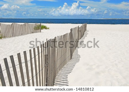 Beautiful white sand beach by fence and ocean - stock photo