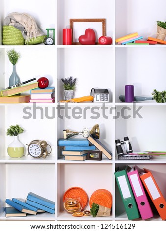 Beautiful white shelves with scattered different home related objects - stock photo