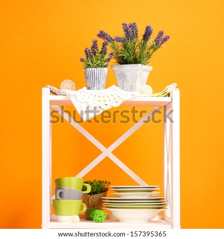 Beautiful white shelves with tableware and decor, on color wall background - stock photo