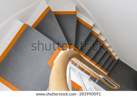 beautiful white staircase with grey carpet and orange highlights - stock photo
