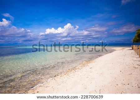 Beautiful white tropical beach on desert island - stock photo