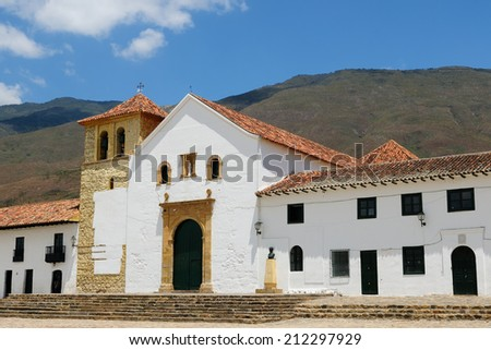 Beautiful white villa with shingle roofs hidden behind walls in colonial Villa de Leyva. Parish church on the plaza central, Colombia, - stock photo
