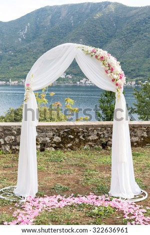 Beautiful white wedding arch decorated with flowers outdoors - stock photo
