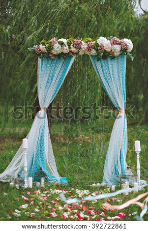 Beautiful white wedding arch decorated with purple and white flowers outdoors, near the willow tree