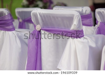 beautiful white wedding chairs decorated with purple bows - stock photo