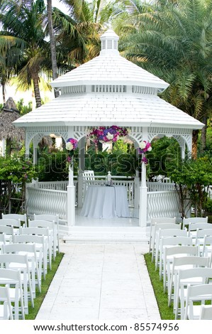 Beautiful white wedding gazebo with flower arrangements decorating - stock photo