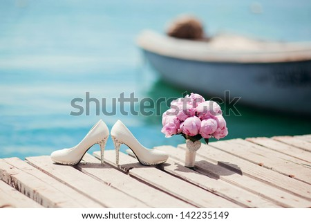 beautiful white wedding shoes and bouquet of flowers by the sea - stock photo
