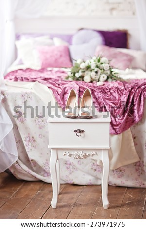 Beautiful white wedding shoes on the white vintage bedside table - stock photo