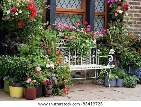 Beautiful white wire bench among flowers - stock photo