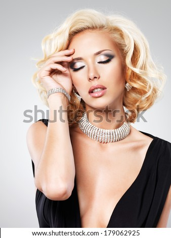 Beautiful white woman with curly  hairstyle and silver bangle -  posing at studio - stock photo