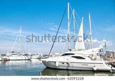 beautiful white yachts at sea port with blue cloudy sky in background