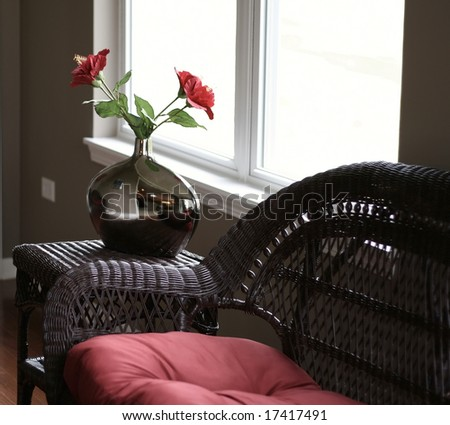 Beautiful wicker furniture with red roses in silver vase - stock photo