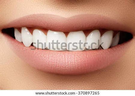 Beautiful wide smile of young fresh woman with great healthy white teeth. Closeup of woman smiling with prefect white teeth on white  - stock photo