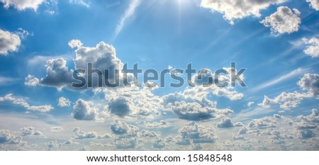 Beautiful wideangle shot of a field of puffy white clouds set against a brilliant blue sky. - stock photo