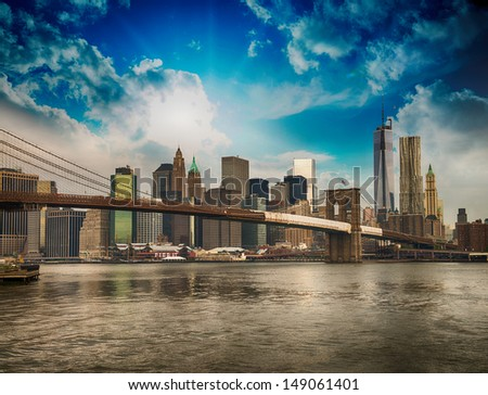 Beautiful wideangle view of Brooklyn Bridge and Manhattan skyline on a overcast summer day. - stock photo