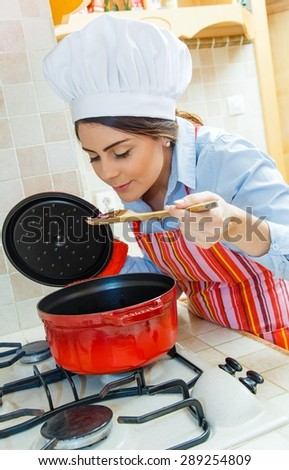 Beautiful wife cooking in the kitchen at home. - stock photo