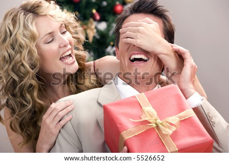 Beautiful wife surprising her husband with a gift for christmas - stock photo