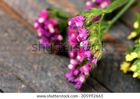 Beautiful wild flowers on wooden table close up