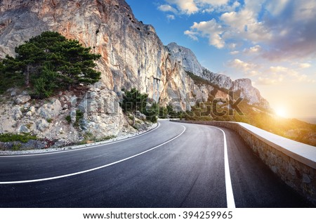Beautiful winding mountain road with a perfect asphalt with high rocks and colorful sunset in summer.  - stock photo