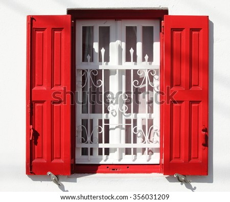 Beautiful window with grille and red shutters in Greece
