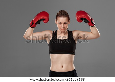 Beautiful winner. Beautiful blond hair woman in red boxing gloves standing on gray background - stock photo