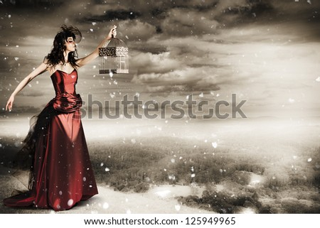 Beautiful Winter Fashion Woman In Creative Makeup Holding Open Bird Cage On Mountain Landscape In A Depiction Of Freedom - stock photo