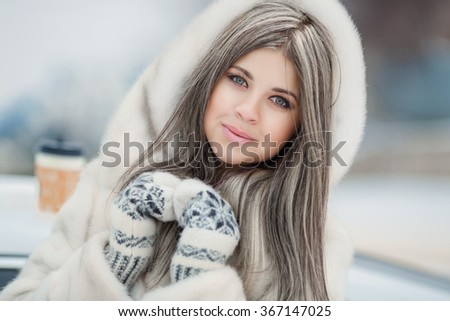 Beautiful winter girl drinking coffee outdoor,  attractive young woman with cocoa cup under snow, winter woman outdoors portrait, girl in winter clothes, soft grain instagram filter like, series - stock photo
