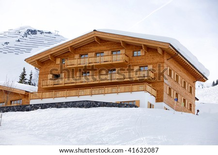 Beautiful winter house on wood and bricks in a snow montain