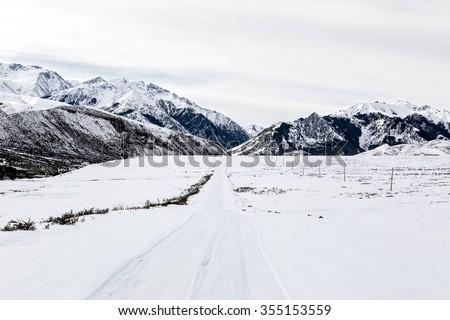 Beautiful winter landscape, an icy road leading towards the Tian-Shan mountain range, Kyrgyzstan.  - stock photo