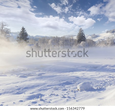 Beautiful winter landscape in the mountain village. Foggy morning - stock photo