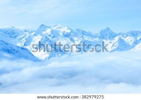 beautiful winter landscape of Caucasus mountains with clouds and blue sky - stock photo