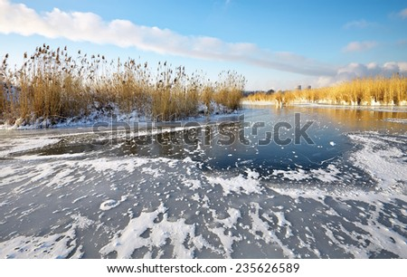 Beautiful winter landscape with frozen lake, reeds and power plant. - stock photo