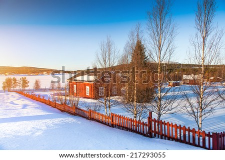 Beautiful winter landscape with house at frozen lake in Scandinavia at sunset - stock photo
