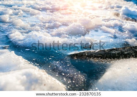 Beautiful winter landscape with ice and snow on the lake. Winter background. Small depth of sharpness - stock photo