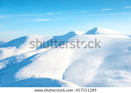 Beautiful winter landscape with snow mountains under blue sky