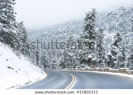 Beautiful winter scene with icy slick road driving situation curving road covered with snow and snowy trees all around - stock photo