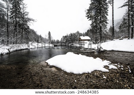 Beautiful winter scenery by the lake and the River. Heavy snow and blizzard is giving the scenery a unique appearance and look. Cottage above the winter river and near the bridge. - stock photo