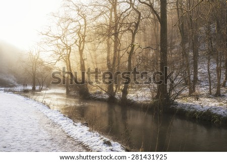 Beautiful Winter snow covered countryside landscape of river flowing with reflections - stock photo