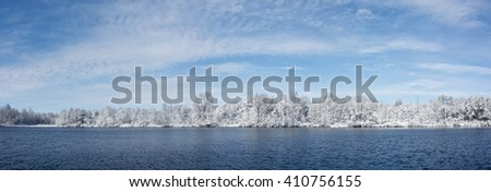 Beautiful winter snow scene with a  tree lined lake with snow clinging to the branches against a bright blue, puffy cloud  sky. - stock photo