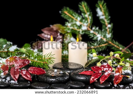 beautiful winter spa concept of zen basalt stones with drops, lilac candles, beads and evergreen branches - stock photo
