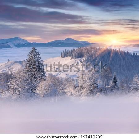 Beautiful winter sunrise in mountain village - stock photo
