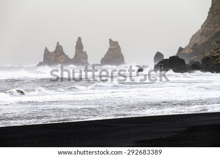 Beautiful winter view of the rocks and rough sea at the black beach of Vik in Iceland - stock photo